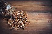 picture of walnut  - Walnut kernels and whole walnuts on rustic old wooden table glass jar - JPG