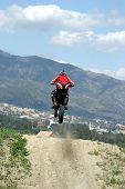 image of moto-x  - orange and red moto x or moto cross bike jumping over hump on dirt track in sy - JPG