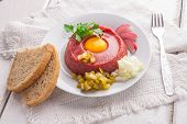 foto of tatar  - Fresh beef tatar with egg on white plate - JPG