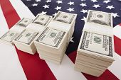 pic of 100 dollars dollar bill american paper money cash stack  - One hundred dollar bills on american flag - JPG