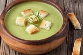 foto of crust  - Healthy green cream broccoli soup with dried crusts in bowl on wooden background - JPG