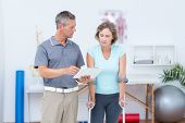 foto of crutch  - Woman using crutch and talking with her doctor in medical office - JPG
