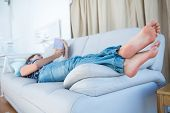 stock photo of peaceful  - Peaceful woman lying on couch reading a book a home in the living room - JPG