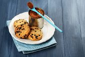 pic of condensation  - Can of boiled condensed milk with spoon and cookies in plate on color wooden table background - JPG