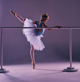 pic of ballet barre  - classic ballet dancer in white tutu posing on one leg at ballet barre on a lilac background - JPG