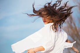 picture of hair motion  - young woman in white shirt with hair in motion - JPG