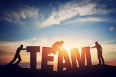 People connect letters to compose the team word. Teamwork concept, idea. Sunset positive light. poster