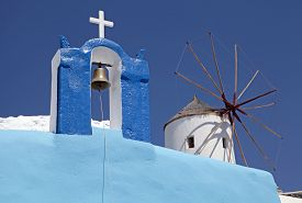 stock photo of blue-bell  - Blue and white bell tower and windmill on blue sky background in Oia village, Santorini, Greece. Selective focus