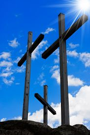 stock photo of crucifixion  - Three wooden crosses on a blue sky with clouds and sun rays on a hill - JPG
