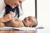 Happy mother playing with baby while changing his diaper. Smiling young woman with baby son on chang poster