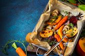 Oven Roasted vegetables with garlic and herbs on the baking tray. Autumn-winter root vegetables. poster