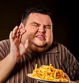 Diet failure of fat man eating french fries fast food. Portrait of overweight person who spoiled hea poster