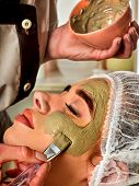 Mud facial mask of woman in spa salon. Massage with clay full face. Girl on with therapy room. Femal poster