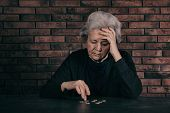 Mature Poor Woman Counting Coins At Table. Space For Text poster