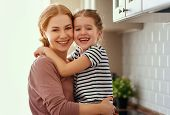 Family Mother And Child Daughter Hugging In Kitchen  . poster