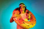 Happy Young Woman In A Cap And In A Rubber Ring With An Icecream On Trendy Blue Neon Studio Backgrou poster