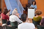 Woman At Podium Chairing Neighborhood Meeting In Community Centre poster