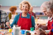 Portrait Of Retired Senior Woman Attending Art Class In Community Centre poster