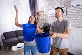Young Husband And Wife With Blue Bucket Collecting Water From Damaged Ceiling In Living Room poster