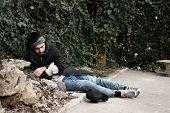 Poor Homeless Man Lying On Street In City poster