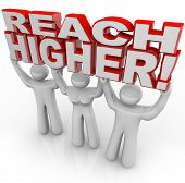 A team of people lift the words Reach Higher to symbolize encouragement to achieve goals and success