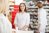 foto of department store  - Happy pharmacist helping customer in drug store - JPG