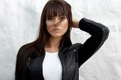 stock photo of straight jacket  - Glamorous young woman in black leather jacket posing near white wall - JPG