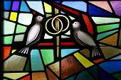 stock photo of stained glass  - a stain glass window depicting two doves with wedding rings - JPG