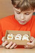 Boy in orange t-shirt look at open box of corrugated cardboard with cookies with almonds and icing s