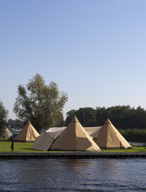 stock photo of tipi  - tipi tents on a dutch camping with blue sky - JPG