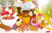 stock photo of crystal salt  - Naturopathy and aromatherapy still life with a pestle and mortar alongside fresh and dried flowers floral potpourri and essential oil extracts in bottles and celestine for crystal healing - JPG