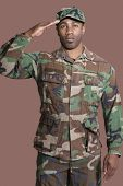 stock photo of corps  - Portrait of a young African American US Marine Corps soldier saluting over brown background - JPG