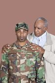 stock photo of corps  - Portrait of African American male US Marine Corps soldier with father over brown background - JPG