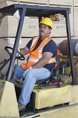 stock photo of forklift driver  - Forklift driver driving in warehouse - JPG