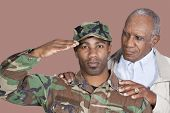 Portrait of US Marine Corps soldier with father saluting over brown background