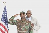 pic of military personnel  - Portrait of father with US Marine Corps soldier saluting American flag over gray background - JPG