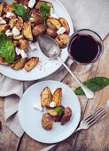 stock photo of baked potato  - Homemade rustic dinner: a glass of wine and a baked potato with soft cheese and fresh basil in a white plate on a wooden board