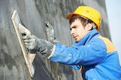 foto of mason  - Young builder worker at facade plastering work during industrial building with putty knife float - JPG