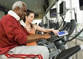 Female instructor assisting senior man on exercise bike at health club