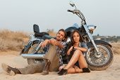 stock photo of scooter  - Happy young love couple on scooter enjoying themselves on trip - JPG