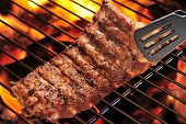 stock photo of pork  - Grilled pork ribs on the flaming grill - JPG