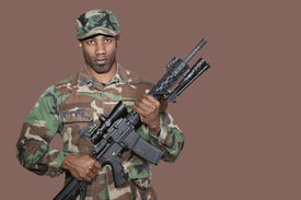 pic of united states marine corps  - Portrait of African American US Marine Corps soldier holding M4 assault rifle over brown background - JPG