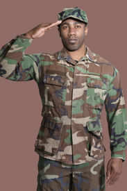 stock photo of united states marine corps  - Portrait of a young African American US Marine Corps soldier saluting over brown background - JPG