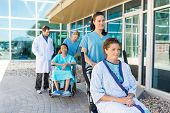 Nurses assisting patients on wheelchairs with doctor standing outside hospital building