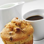 closeup of a muffin in a plate and a cup of coffee on a set table