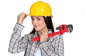 Tradeswoman holding  pipe wrench