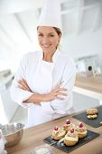 stock photo of confectioners  - Successful woman confectioner in professional kitchen - JPG