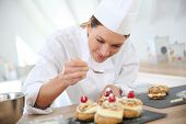stock photo of confectioners  - Professional cook spreading powdered sugar on cream puffs - JPG