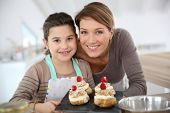 stock photo of confectioners  - Mother and daughter preparing cream puffs - JPG