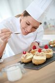 image of cream puff  - Professional cook spreading powdered sugar on cream puffs - JPG